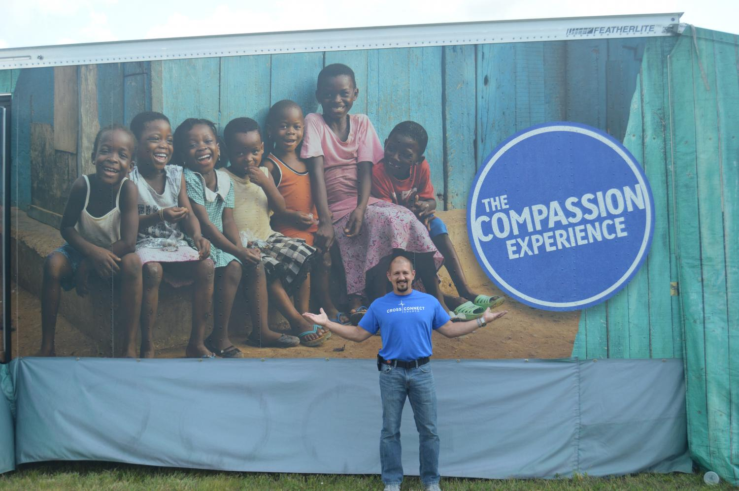 Tommy Theisen, pastor at CrossConnect, poses in front of poster after briefly explaining the purpose of the project.