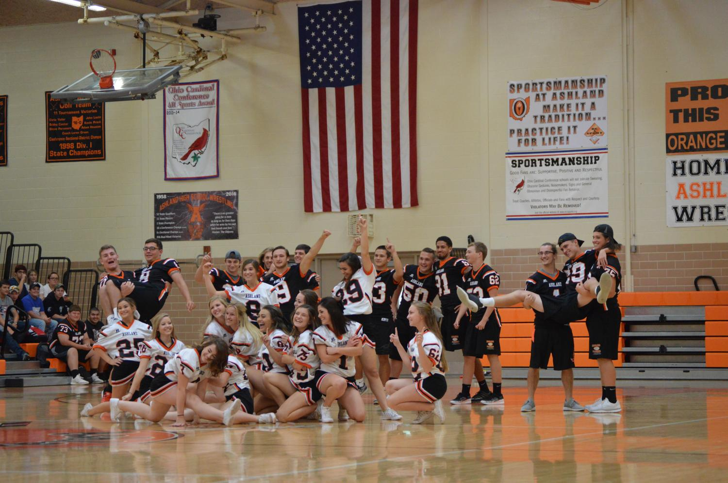Ashland High School football players and cheerleaders dance to a medley during the homecoming assembly.