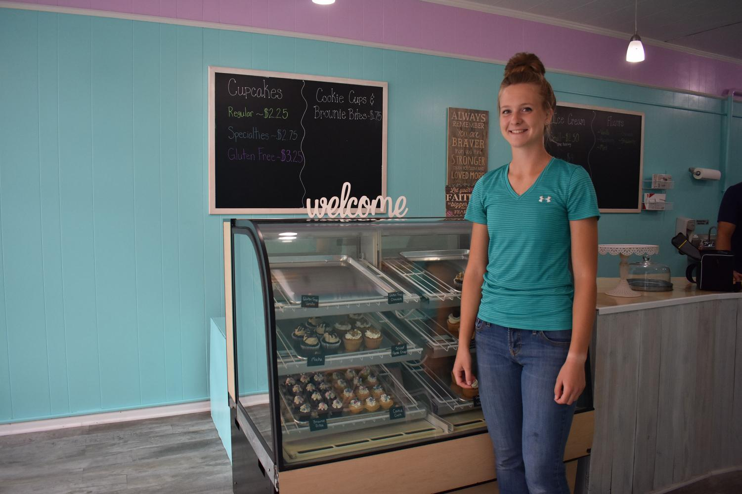 Andra S., owner of Priceless Treats, poses by her cupcakes on the bakery's opening day.