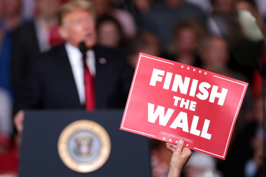 Citizen holds up sign supporting border wall at Make America Great Again campaign rally in Arizona.